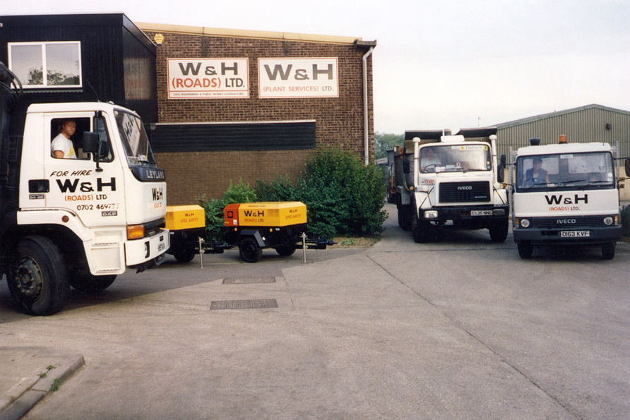 An old image of the W&H Roads head office with large vehicles parked outside